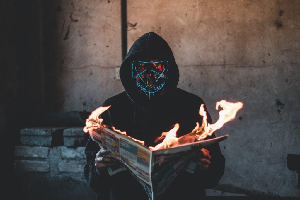 Ein maskierter Mann mit brennender Zeitung