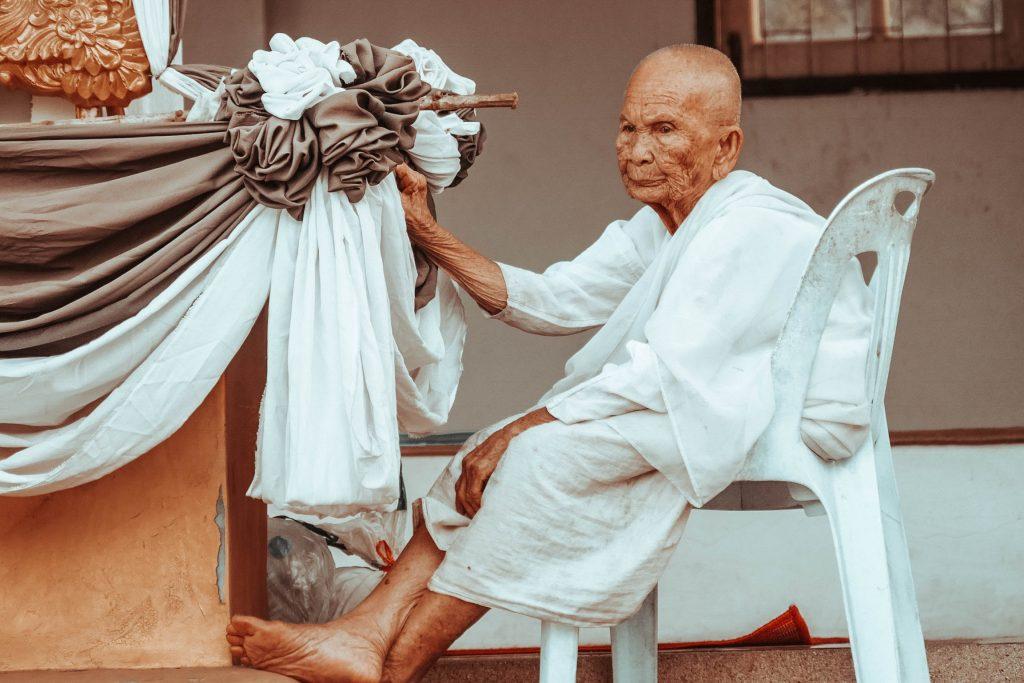 Ein alter Mann sitzt auf dem Stuhl
