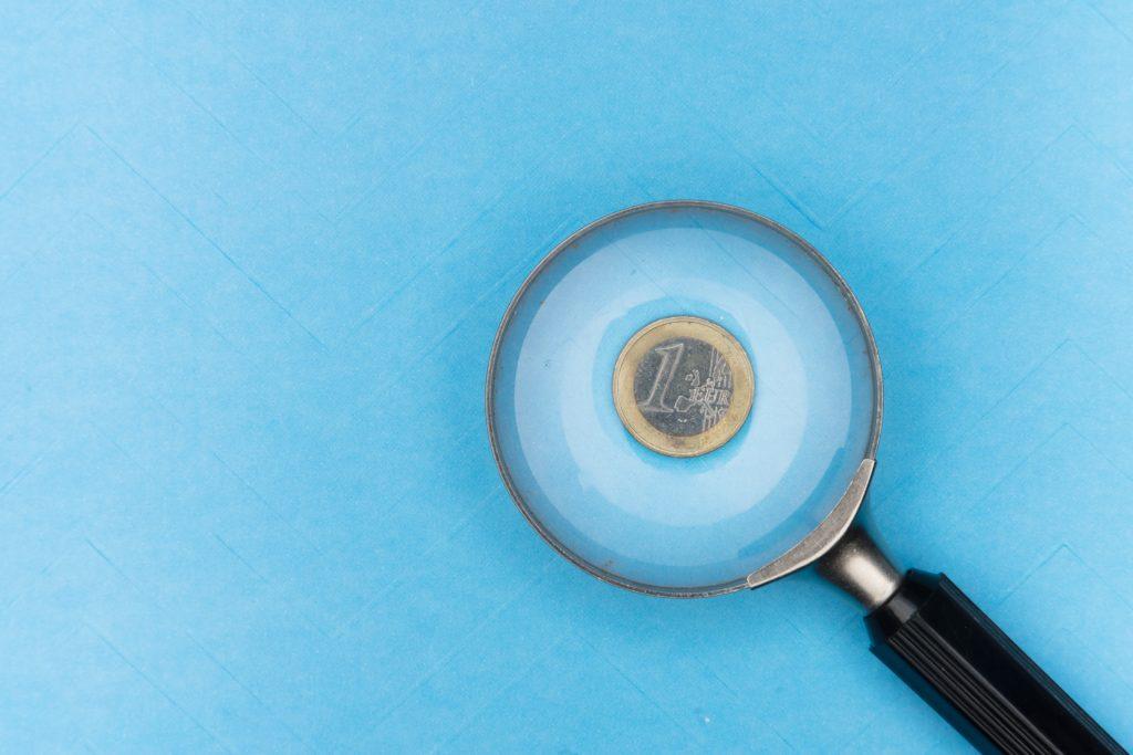 Euromünze unter einer Lupe