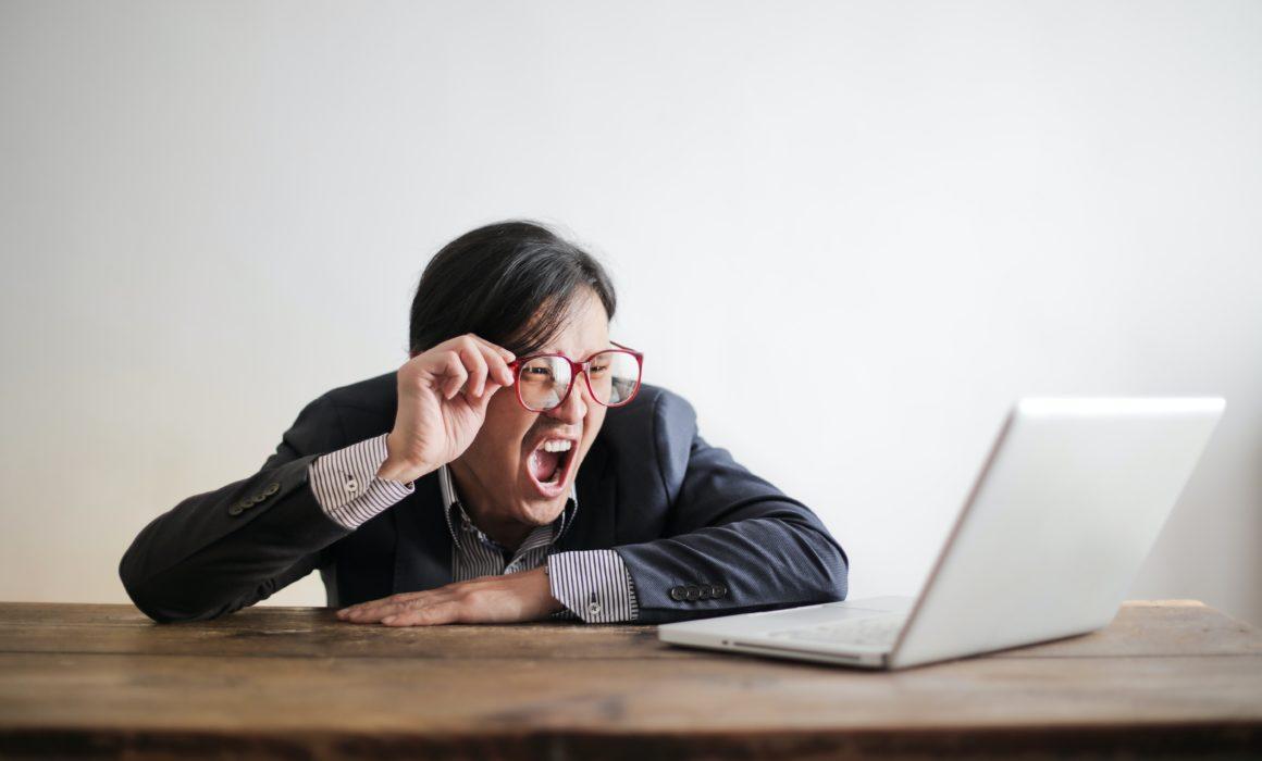 Mann schreit Laptop an