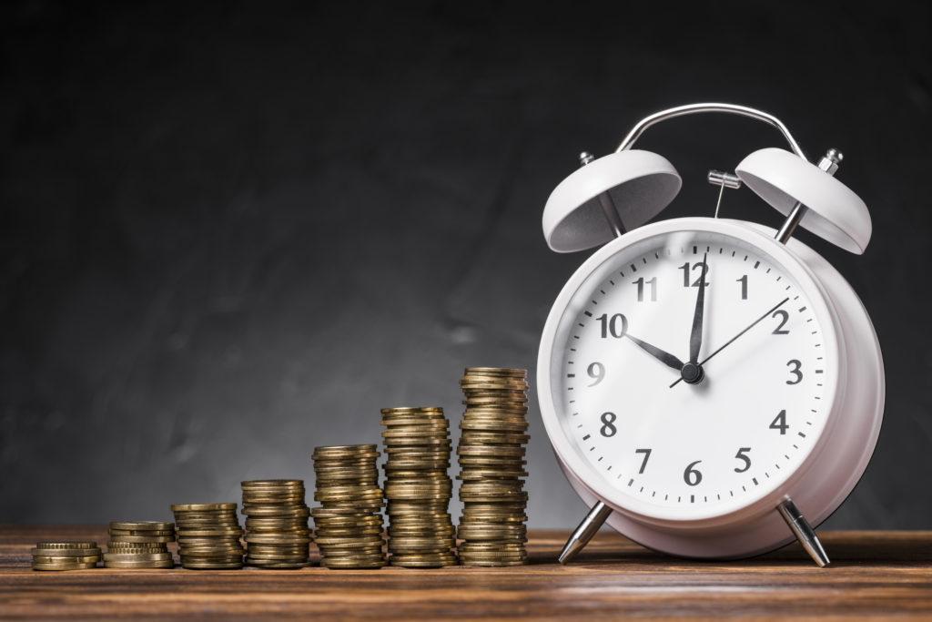 Geldstapel mit Uhr