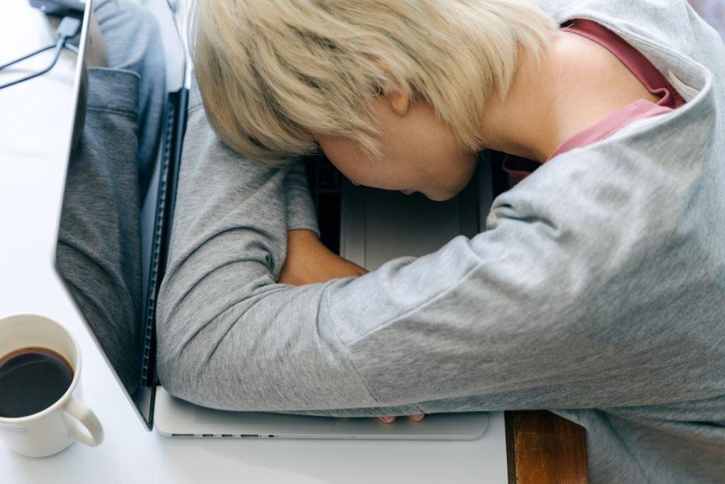 Frau schläft auf Laptop