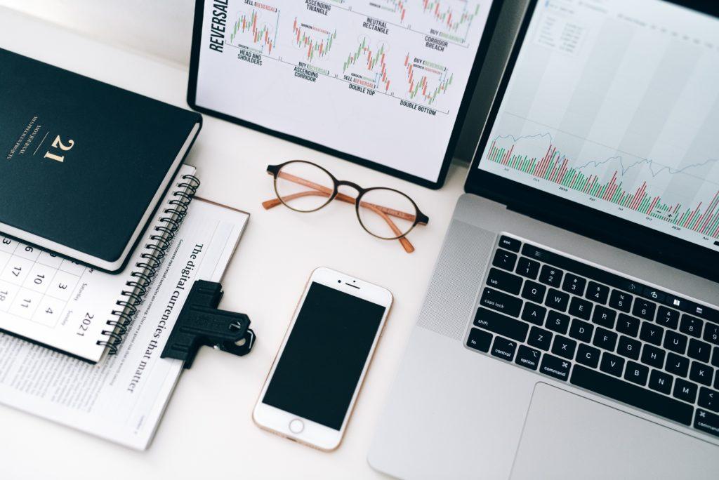 Kalender, Brille, Smartphone und Laptop auf weisem Tisch