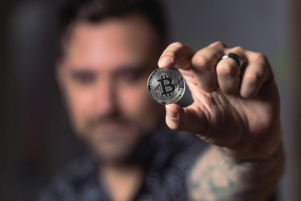 Mann hält silberne Bitcoin Münze in die Kamera