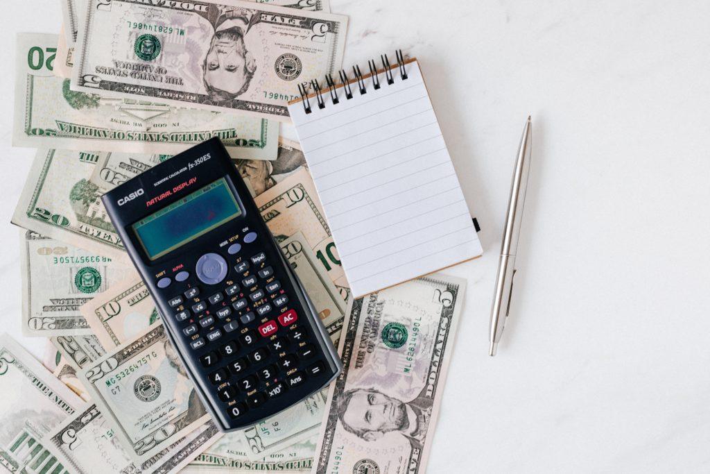 Taschenrechner und Notizbuch auf Bargeld