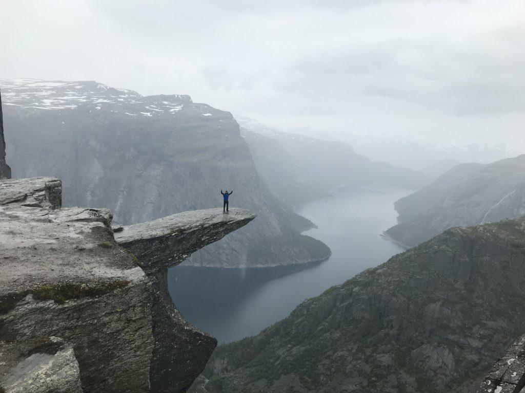Mann steht auf großem Felsen