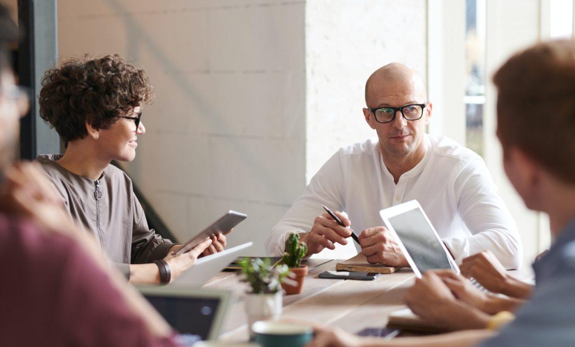 Mann im Hemd am Tisch mit anderen