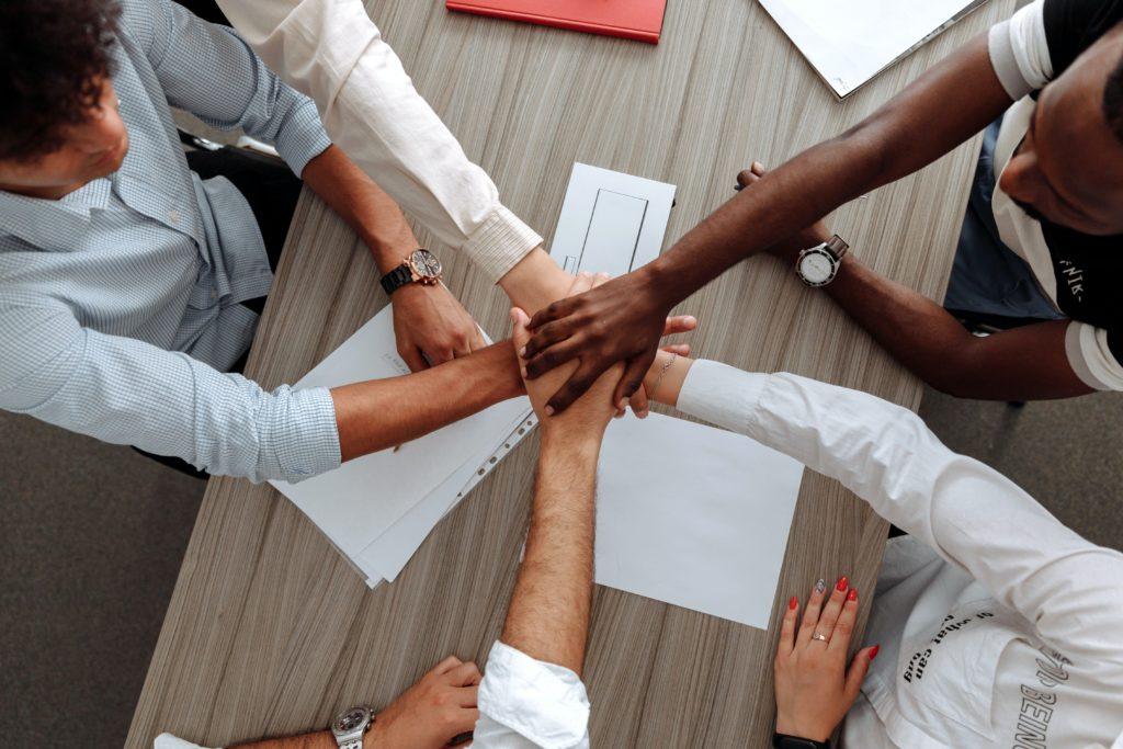 Personen halten die Hände zusammen